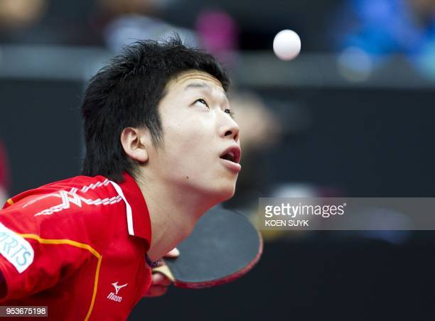 Japan's Jun Mizutani eyes the ball as he plays against German's Zoltan FejerKonnerth during their men's singles 3rdround match at the 2011 World...