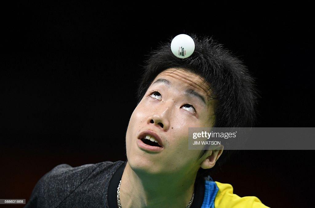 TOPSHOT - Japan's Jun Mizutani eyes the ball as he serves against Belarus' Vladimir Samsonov in their men's singles bronze medal table tennis match at the Riocentro venue during the Rio 2016 Olympic Games in Rio de Janeiro on August 11, 2016. / AFP / Jim WATSON