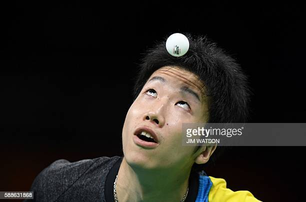 TOPSHOT Japan's Jun Mizutani eyes the ball as he serves against Belarus' Vladimir Samsonov in their men's singles bronze medal table tennis match at...