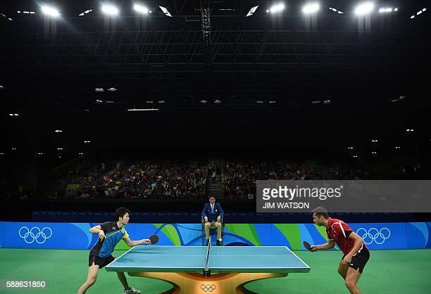 Japan's Jun Mizutani hits a shot against Belarus' Vladimir Samsonov in their men's singles bronze medal table tennis match at the Riocentro venue...