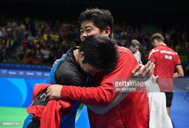 Japan's Jun Mizutani hugs his coach as he celebrates beating Belarus' Vladimir Samsonov in their men's singles bronze medal table tennis match at the...