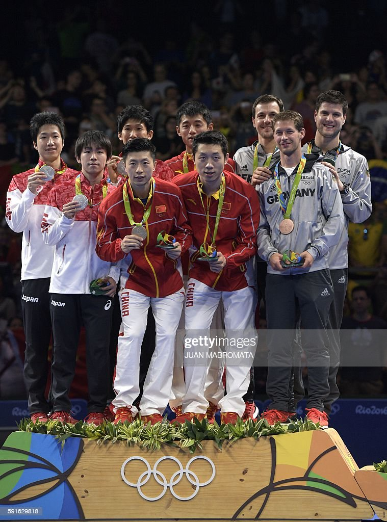 Japan's Jun Mizutani, Japan's Koki Niwa and Japan's Maharu Yoshimura (back) pose with their silver medals, China's Ma Long (front), China's Zhang Jike (back), and China's Xu Xin (front) pose with their gold medals, and Germany's Timo Boll (back), Germany's Bastian Steger (front), and Germany's Dimitrij Ovtcharov (back) pose with their bronze medals after the final men's team table tennis match at the Riocentro venue during the Rio 2016 Olympic Games in Rio de Janeiro on August 17, 2016. / AFP / Juan Mabromata