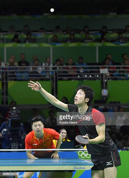 Japan's Jun Mizutani tosses the ball for a serve in his singles semifinal match against Ma Long of China at the Rio Olympics on Aug 11 2016 Ma won...