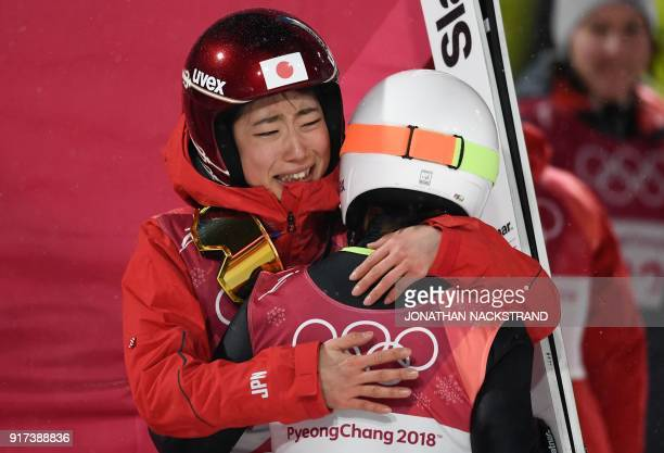 Japan's Kaori Iwabuchi hugs her compatriot Sara Takanashi after the latter took third place in the women's normal hill individual ski jumping event...