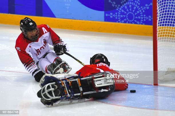 Japan's Kazuhiro Takahashi shoots against Norway's goalkeeper Kjell Christian Hamar during the ice hockey classification game between Norway and...