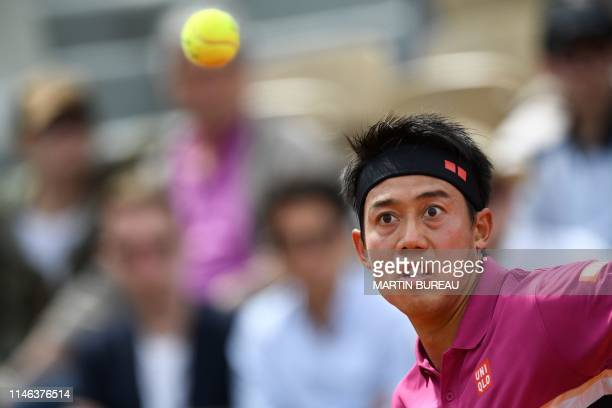 Japan's Kei Nishikori eyes the ball as he hits a return to France's Quentin Halys during their men's singles first round match on day 1 of The Roland...