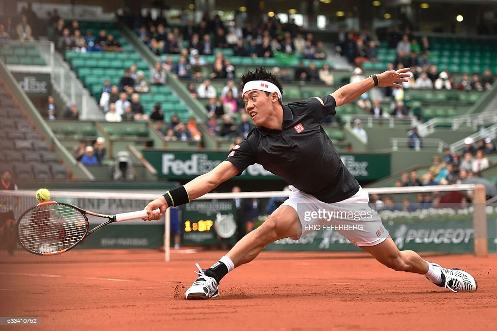 TOPSHOT - Japan's Kei Nishikori hits a return to Italy's Simone Bolelli during their men's first round match at the Roland Garros 2016 French Tennis Open in Paris on May 22, 2016. / AFP / Eric FEFERBERG