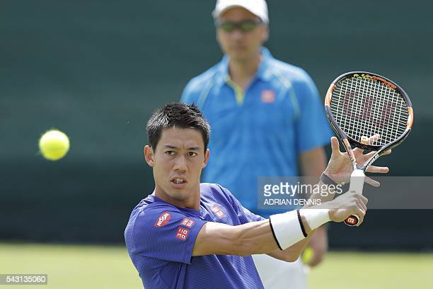 Japan's Kei Nishikori plays a shot on a practice court under the watch of his US coach Michael Chang at The All England Tennis Club in Wimbledon...