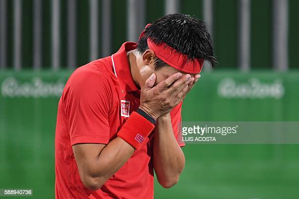 Japan's Kei Nishikori reacts after winning the men's singles quarter-final tennis match against France's Gael Monfils at the Olympic Tennis Centre of...