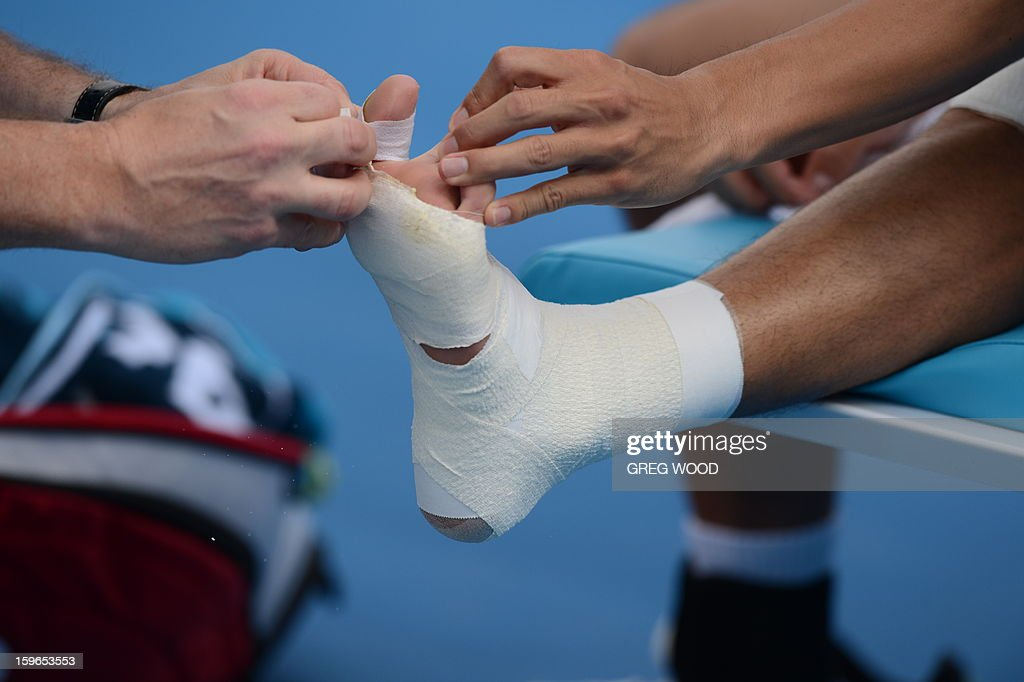 Japan's Kei Nishikori receives treatment during his men's singles match against Evgeny Donskoy of Russia on the fifth day of the Australian Open tennis tournament in Melbourne on January 18, 2013.