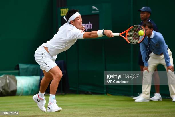 Japan's Kei Nishikori returns against Italy's Marco Cecchinato during their men's singles first round match on the first day of the 2017 Wimbledon...