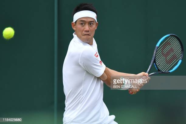 Japan's Kei Nishikori returns against US player Steve Johnson during their men's singles third round match on the sixth day of the 2019 Wimbledon...