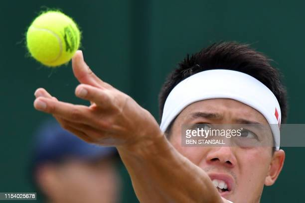 Japan's Kei Nishikori serves to US player Steve Johnson during their men's singles third round match on the sixth day of the 2019 Wimbledon...