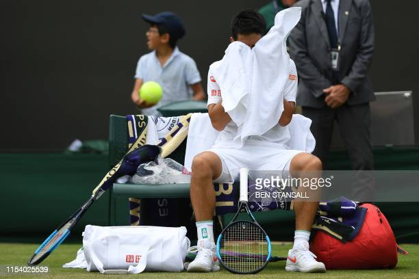 Japan's Kei Nishikori sits after beating US player Steve Johnson during their men's singles third round match on the sixth day of the 2019 Wimbledon...