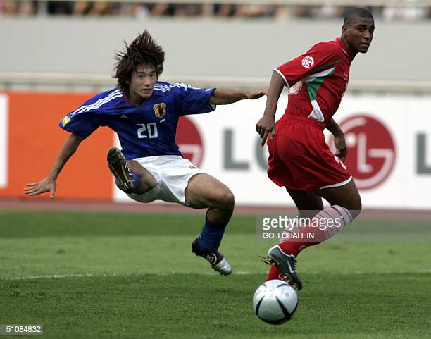 Japan's Keiji Tamada tussles with Oman's Mohamed AlNoobi during the Asian Cup Group D match 20 July 2004 in the southwestern Chinese city of...
