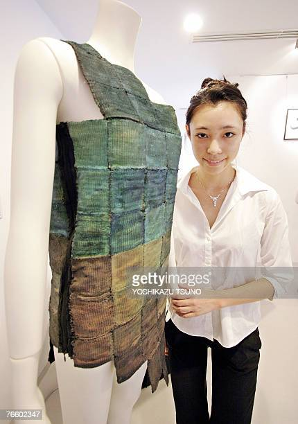 Japan's Keio University postgraduate student Midori Shibuya displays a dress made of hightech fabric Fabcell made of woven square textiles dyed by...