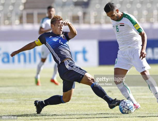 Japan's Keisuke Honda and Iraq's Ali Adnan vie for the ball in the first half of a World Cup qualifier in Tehran Iran on June 13 2017 ==Kyodo
