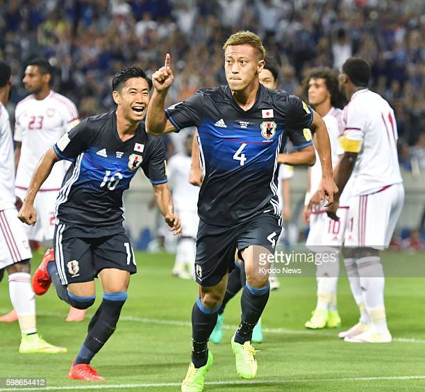 Japan's Keisuke Honda celebrates with teammate Shinji Kagawa after scoring the opener during the first half of the 2018 World Cup Asian qualifier...