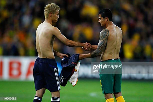 Japan's Keisuke Honda exchanges jersey's with Australian player Tim Cahill at the conclusion of the 2014 World Cup qualifying football match between...