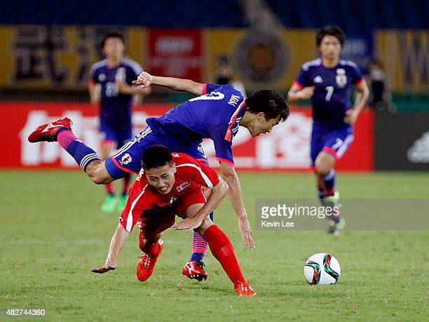 Japan's Kensuke Nagai and DPR Korea's Kang Kuk Chol vie for the ball during EAFF East Asian Cup 2015 final round on August 2 2015 in Wuhan China