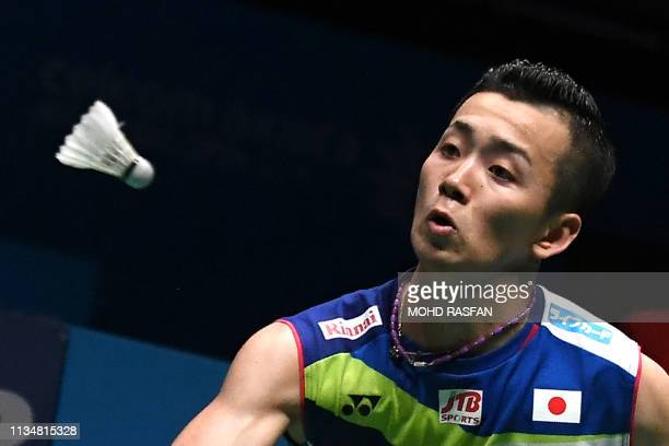 Japan's Kenta Nishimoto hits a return against Denmark's Rasmus Gemke during their men's singles match at the Malaysia Open badminton tournament in...