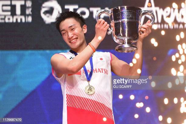 Japan's Kento Momota poses with his trophy after victory over Denmark's Viktor Axelsen in the mens singles final of the All England Open Badminton...