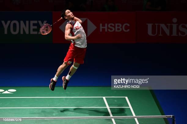 Japan's Kento Momota prepares to smash against Thailand's Khosit Phetpradab during the men's singles final at the Japan Open Badminton Championships...