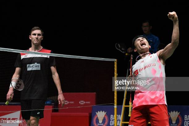 Japan's Kento Momota reacts after winning against Denmark's Viktor Axelsen during their men's singles final match at the Malaysia Open badminton...