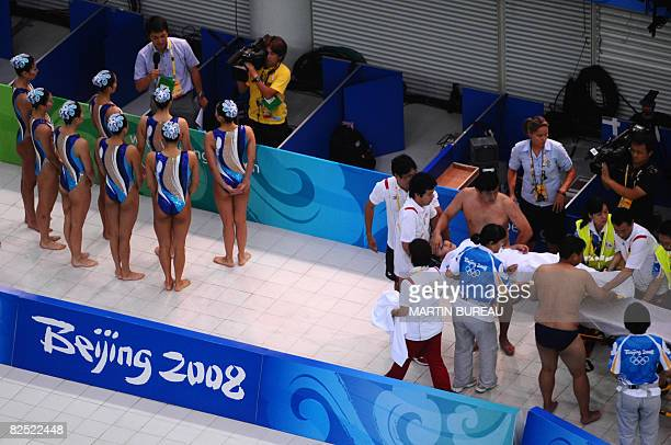 Japan's Kobayashi Hiromi is carried on a stretcher after she had hyperventilated during the synchronized swimming team free routine final event of...