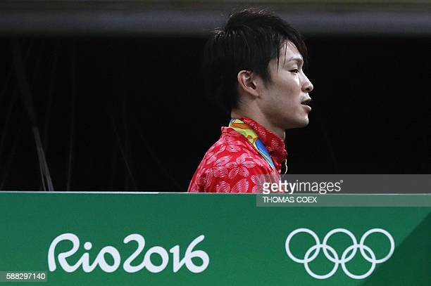 Japan's Kohei Uchimura walks with his gold medal after the men's individual all-around final of the Artistic Gymnastics at the Olympic Arena during...