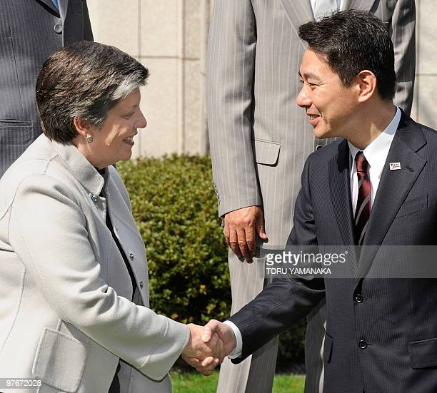 Japan's Land Infrastructure Transport and Tourism Minister Seiji Maehara shakes hands with US Homeland Security Secretary Janet Napolitano during the...