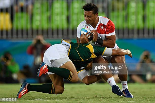 Japan's Lomano Lemeki is tackled by South Africa's Juan de Jongh in the mens rugby sevens bronze medal match between Japan and South Africa during...