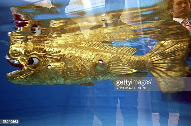Japan's machinery giant Mitsubishi Heavy Industries' subsidiary Ryoumei Engineering unveils the new fish swimming robot in a fish tank at the...
