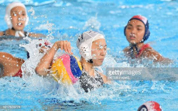 Japan's Marina Tokumoto fights for the ball against Indonesia in the womens water polo Preliminary Group A event during the 2018 Asian Games in...