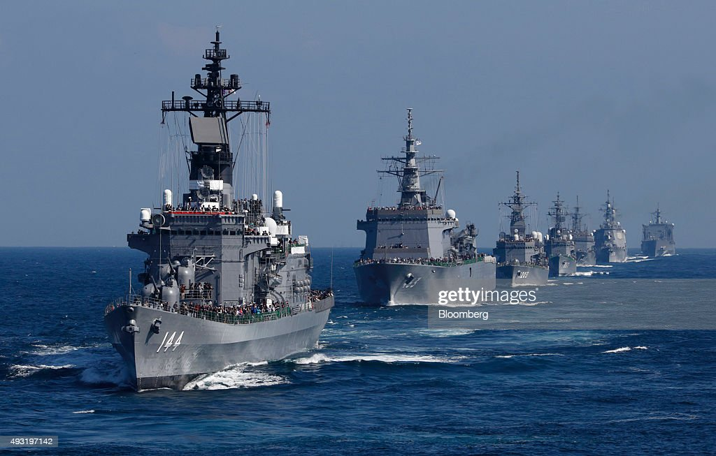 Japan's Maritime Self-Defense Force destroyer ship Kurama, left, leads a troop of vessels during a review at Sagami Bay, off Yokosuka, Kanagawa Prefecture, Japan, on Sunday, Oct. 18, 2015. Prime Minister Shinzo Abe's public approval ratings declined after the passage of legislation allowing Japan to send troops to fight in overseas conflicts for the first time since World War II. Photographer: Tomohiro Ohsumi/Bloomberg via Getty Images