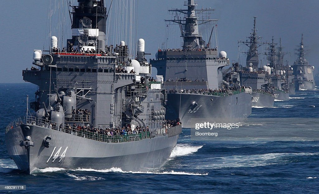 Japan's Maritime Self-Defense Force destroyer ship Kurama, left, leads a troop of vessels during a fleet review at Sagami Bay, off Yokosuka, Kanagawa Prefecture, Japan, on Sunday, Oct. 18, 2015. Prime Minister Shinzo Abes public approval ratings declined after the passage of legislation allowing Japan to send troops to fight in overseas conflicts for the first time since World War II. Photographer: Tomohiro Ohsumi/Bloomberg via Getty Images