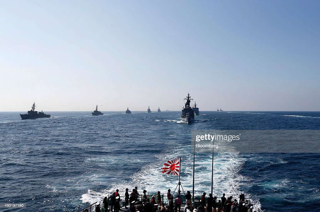 Japan's Maritime Self-Defense Force destroyer ship Kurama, right, leads a troop of vessels during a review at Sagami Bay, off Yokosuka, Kanagawa Prefecture, Japan, on Sunday, Oct. 18, 2015. Prime Minister Shinzo Abe's public approval ratings declined after the passage of legislation allowing Japan to send troops to fight in overseas conflicts for the first time since World War II. Photographer: Tomohiro Ohsumi/Bloomberg via Getty Images