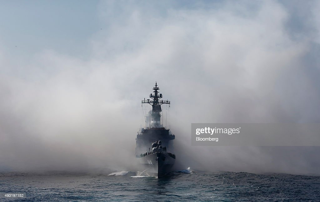 Japan's Maritime Self-Defense Force destroyer ship Kurama sails through the smoke of anti-IR missile flares during a review at Sagami Bay, off Yokosuka, Kanagawa Prefecture, Japan, on Sunday, Oct. 18, 2015. Prime Minister Shinzo Abe's public approval ratings declined after the passage of legislation allowing Japan to send troops to fight in overseas conflicts for the first time since World War II. Photographer: Tomohiro Ohsumi/Bloomberg via Getty Images