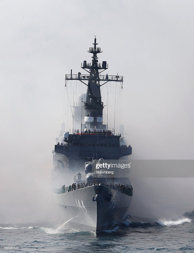 Japan's Maritime Self-Defense Force destroyer ship Kurama sails through smoke from anti-IR missile flares during a fleet review at Sagami Bay, off Yokosuka, Kanagawa Prefecture, Japan, on Sunday, Oct. 18, 2015. Prime Minister Shinzo Abe's public approval ratings declined after the passage of legislation allowing Japan to send troops to fight in overseas conflicts for the first time since World War II. Photographer: Tomohiro Ohsumi/Bloomberg via Getty Images