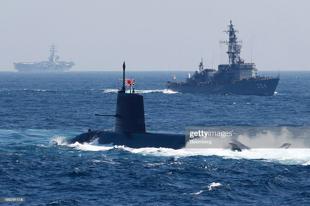 Japan's Maritime Self-Defense Force Kokuryu submarine, front, sails past a vessel during a fleet review at Sagami Bay, off Yokosuka, Kanagawa Prefecture, Japan, on Sunday, Oct. 18, 2015. Prime Minister Shinzo Abeâs public approval ratings declined after the passage of legislation allowing Japan to send troops to fight in overseas conflicts for the first time since World War II. Photographer: Tomohiro Ohsumi/Bloomberg via Getty Images
