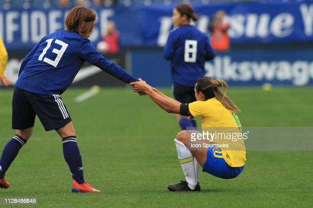 Japan's May Ikejiri helps Brazil's Marta after a foul during a SheBelieves Cup match between Brazil and Japan March 2 at Nissan Stadium in Nashville...