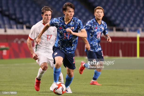 Japan's midfielder Ao Tanaka is marked by Mexico's midfielder Sebastian Cordova during the Tokyo 2020 Olympic Games men's group A first round...