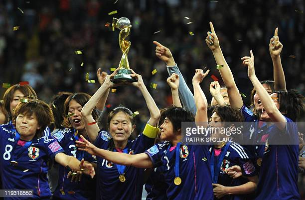 Japan's midfielder Homare Sawa and teammates celebrate with the trophy after the FIFA Women's Football World Cup final match Japan vs USA on July 17...