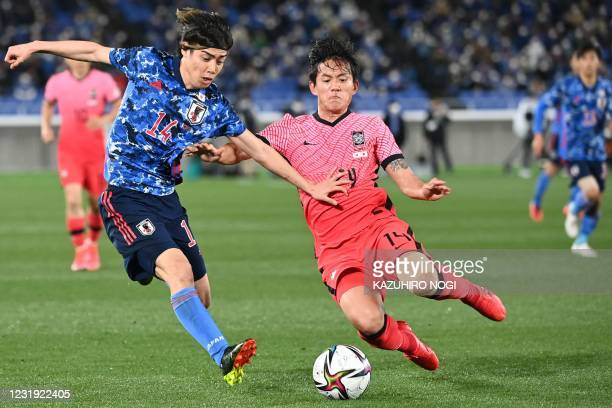 Japan's midfielder Junya Ito and South Korea's defender Hong?Chul fight for the ball during a friendly football match against South Korea at Nissan...
