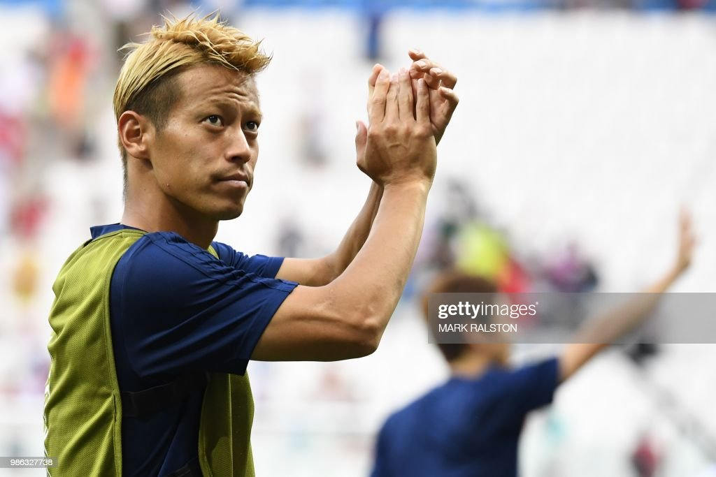 TOPSHOT - Japan's midfielder Keisuke Honda celebrates their qualification for the next round at the end of the Russia 2018 World Cup Group H football match between Japan and Poland at the Volgograd Arena in Volgograd on June 28, 2018. (Photo by Mark RALSTON / AFP) / RESTRICTED