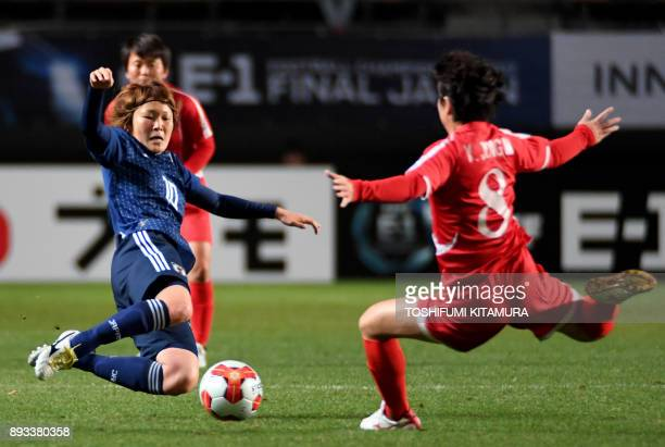 Japan's midfielder Mizuho Sakaguchi fights for the ball with North Korea's midfielder Yu JongIm during the women's football match between Japan and...