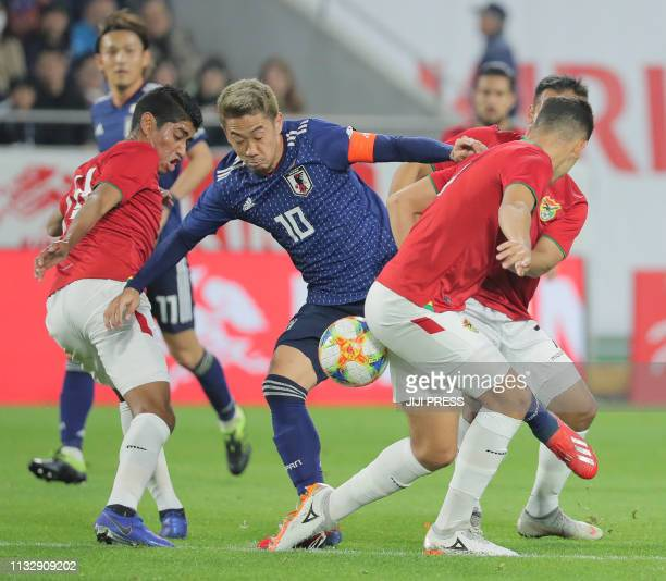 Japan's midfielder Shinji Kagawa attempts to break through Bolivian defense during their international friendly football match in Kobe on March 26...
