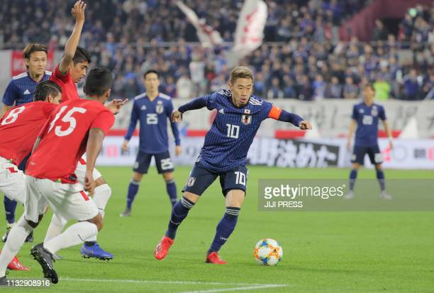 Japan's midfielder Shinji Kagawa keeps the ball against Bolivia during their international friendly football match in Kobe on March 26 2019 / Japan...