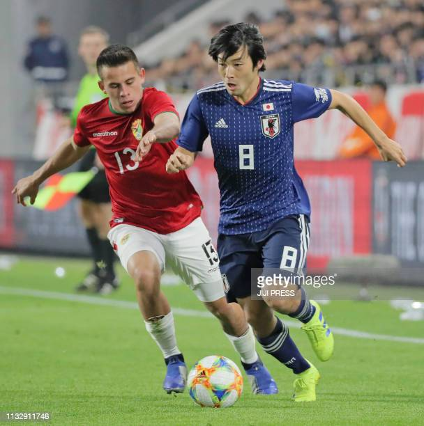 Japan's midfielder Shoya Nakajima and Bolivia's forward Henry Vaca fight for the ball during their international friendly football match in Kobe on...