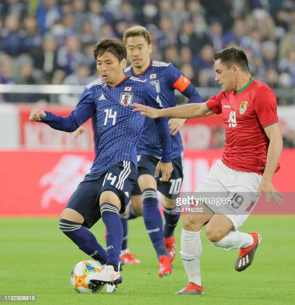 Japan's midfielder Takashi Inui and Bolivia's forward Leonardo Vaca fight for the ball during their international friendly football match in Kobe on...